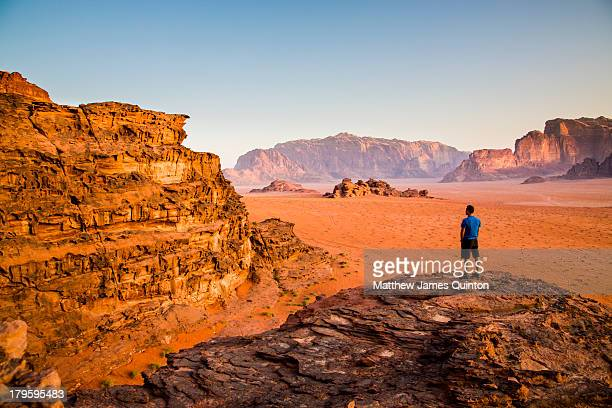 Man on cliff edge looking out at desert