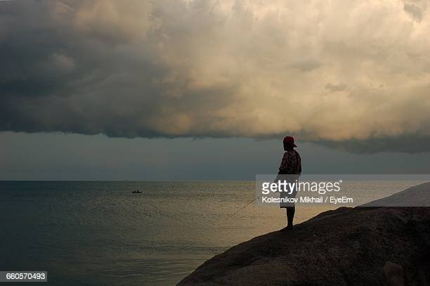 Man On Cliff Fishing In Sea Against Cloudy Sky