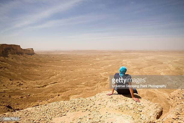 Man on Cliff's Edge in Desert