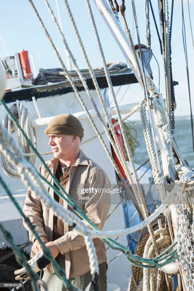 Man on commercial fishing boat putting on gloves : Foto stock