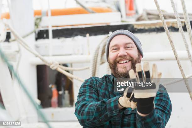 Man on commercial fishing boat putting on gloves