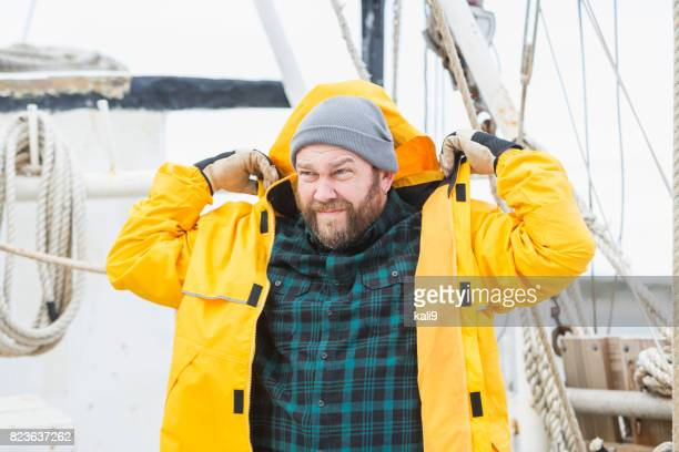 Man on commercial fishing boat putting on raincoat