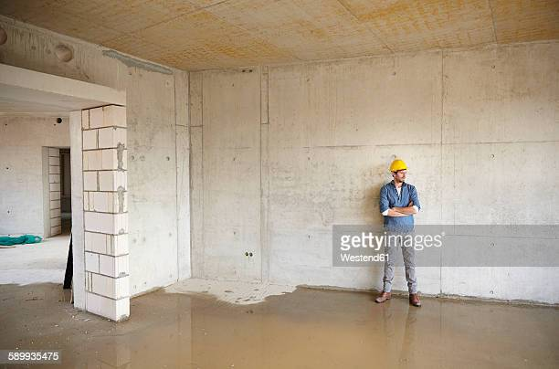 Man on construction site standing at large puddle