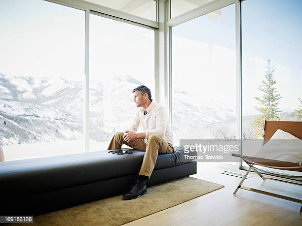 Man on couch in modern home with digital tablet
