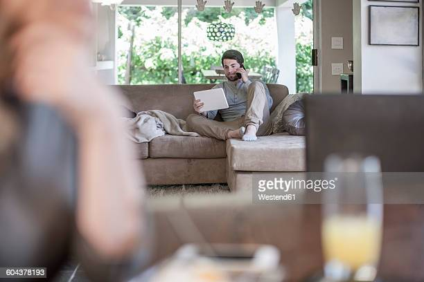 Man on couch looking at digital tablet and talking on cell phone with woman in foreground