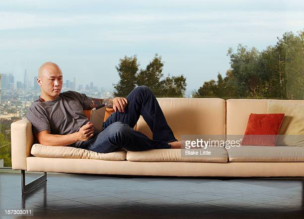 Man on couch reading on a digital tablet.