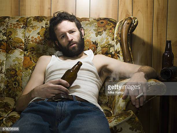 Man on couch with beer bottle and cigarette