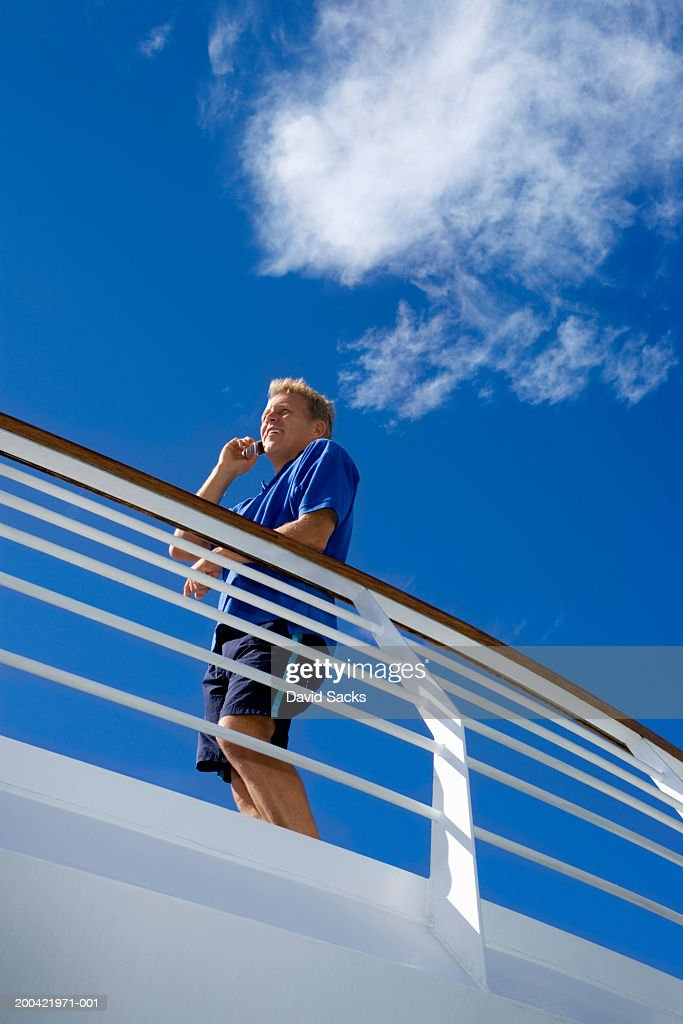 Man On Cruise Ship Using Mobile Phone Stock Photo Getty Images - How to use cell phone on cruise ship