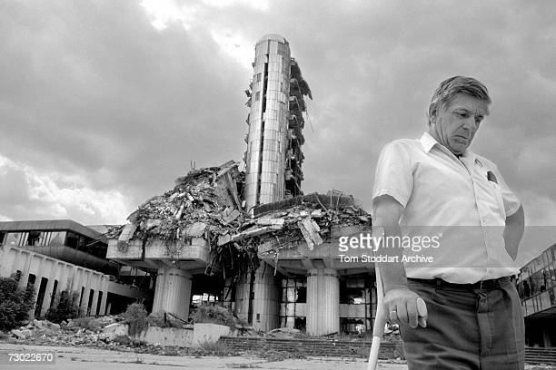 A man on crutches having been wounded by a shell stands deep in thought outside the destroyed Oslobodenje newspaper building in Sarajevo During the...