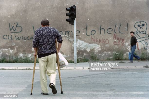 """Man on crutches walks across Sniper Alley towards graffitis reading """"Welcome to hell"""" at Sarajevo on August 28, 1993."""