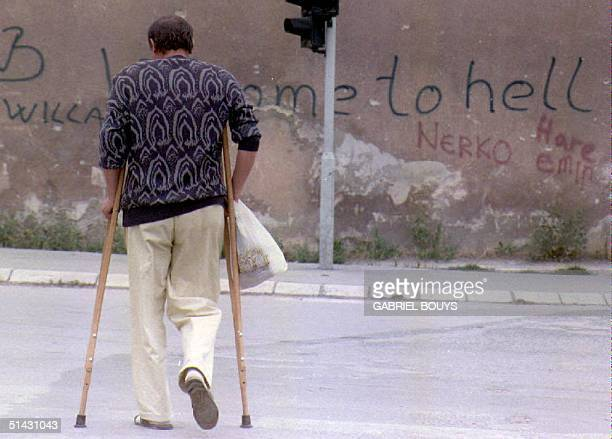"""Man on crutches walks across the area of Sarajevo known as """"Sniper Alley"""" 28 August 1993, near a wall with graffiti that reads """"Welcome to Hell."""" The..."""