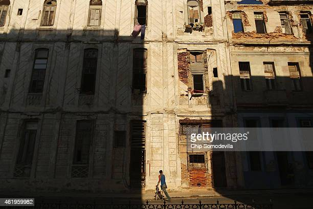 A man on crutches walks past deteriorating buildings along the Malecon oceanfront drive January 21 2015 in Havana Cuba Cuba and the United States are...