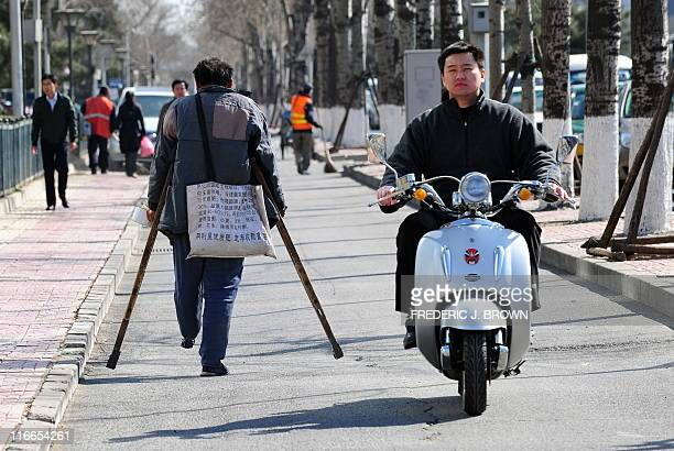 A man on crutches with a bag around his shoulder made from a sack of fertilizer walks down a bicycle path in Beijing on March 22 2011 past a man on...