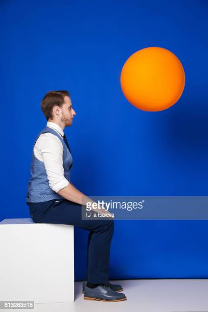 man on cube and orange ball - multi colored suit stock photos and pictures
