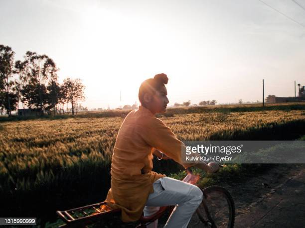 man on cycle against farmland - chandigarh stock pictures, royalty-free photos & images