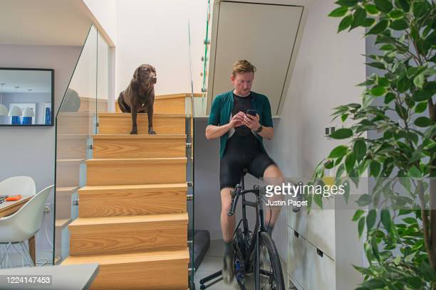 man on cycling trainer at home - sports training stock pictures, royalty-free photos & images