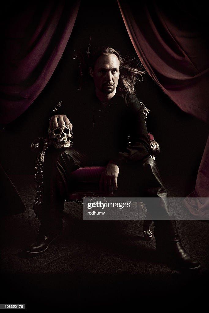 Homem no escuro Trono com Crânio : Foto de stock