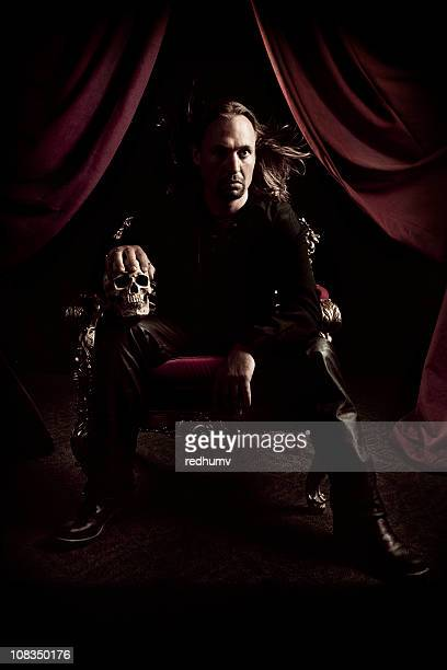man on dark throne with skull - throne stock pictures, royalty-free photos & images