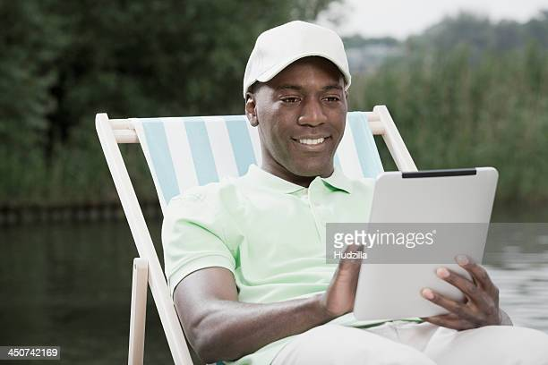 Man on deck chair using digital tablet by lake
