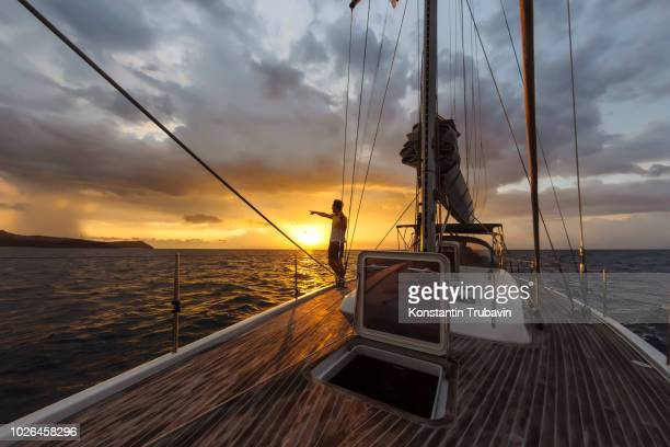 man on deck of large yacht pointing at sunset on horizon, lombok, indonesia - ricchezza foto e immagini stock