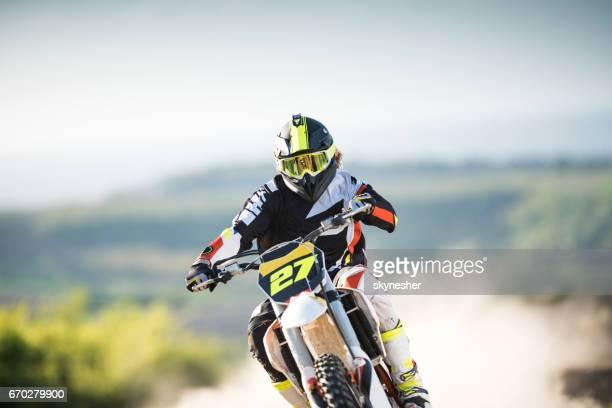 Man on dirt bike racing in nature.
