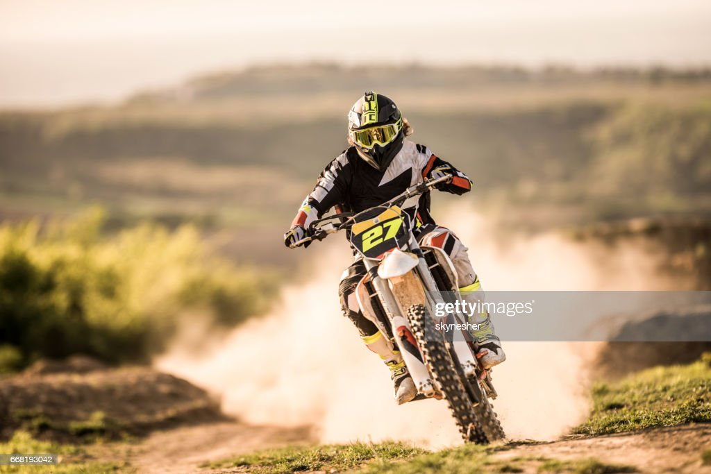 Man on dirt bike racing on dirt road in nature. : Stock Photo