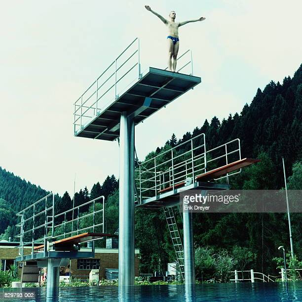 Man on diving board with arms outstretched