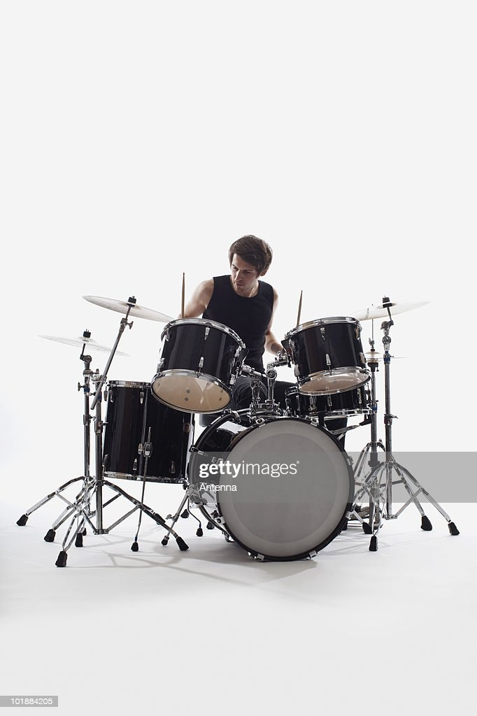 A man on drums performing, studio shot, white background, back lit : Stock Photo