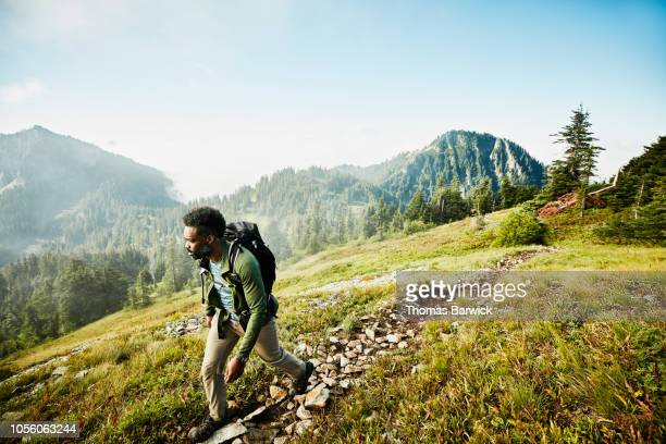 man on early morning hike up mountainside - outdoor pursuit stock pictures, royalty-free photos & images