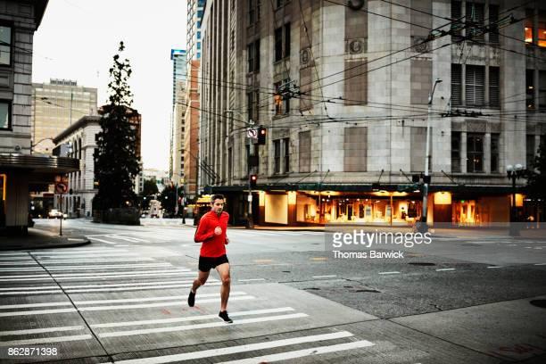 Man on early morning run on empty city street