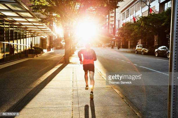 man on early morning run on empty city street - image foto e immagini stock