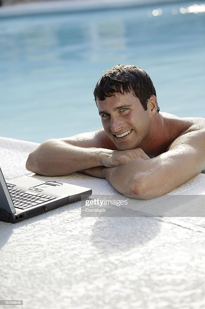 Man on edge of swimming pool with laptop computer : Stockfoto