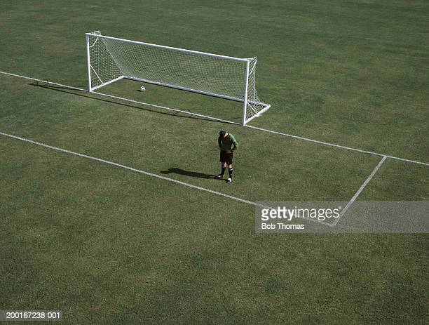 Man on empty football pitch by goal, head bowed, elevated view
