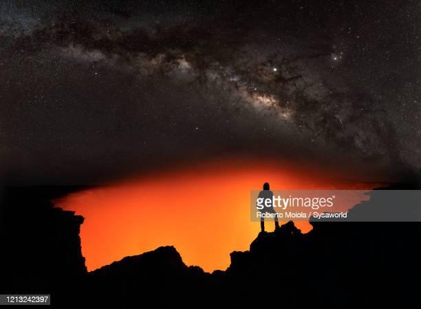 man on erta ale volcano admiring lava and milky way, danakil, afar, ethiopia - vulcano attivo foto e immagini stock
