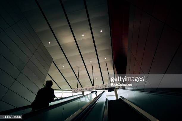 man on escalator moving towards 'move your mind' led screen - spiritual enlightenment stock pictures, royalty-free photos & images