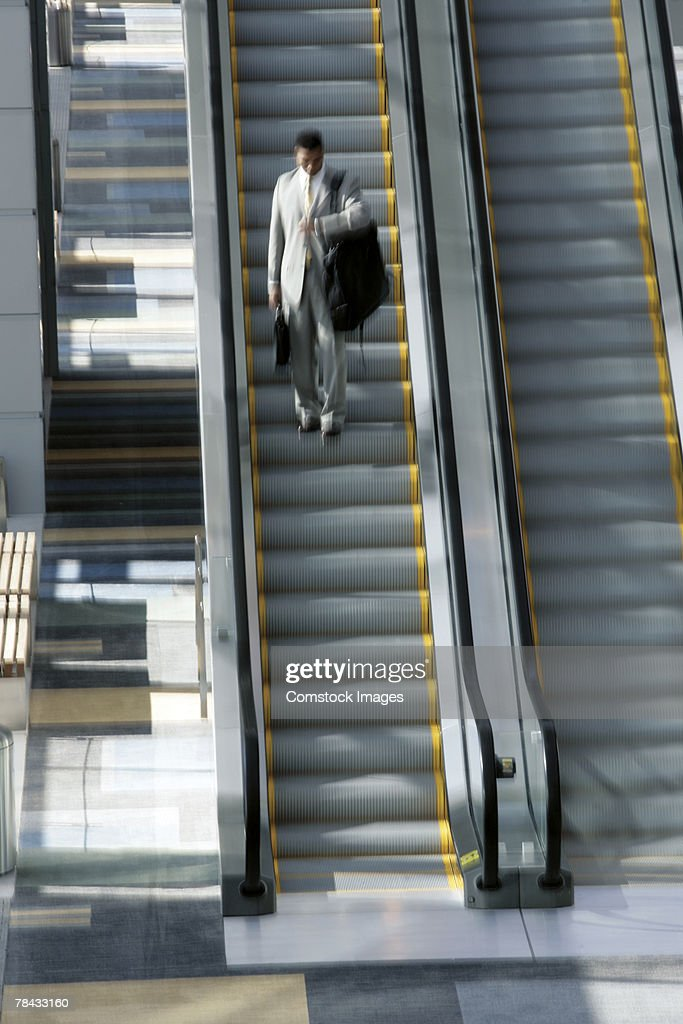Man on escalator with luggage : Stockfoto