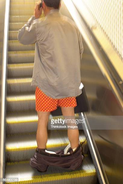 Man on escalator with pants down