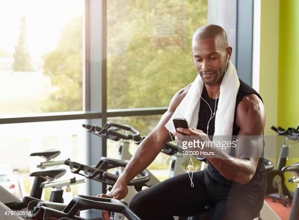 Man on exercise bike in gym looking at smart phone