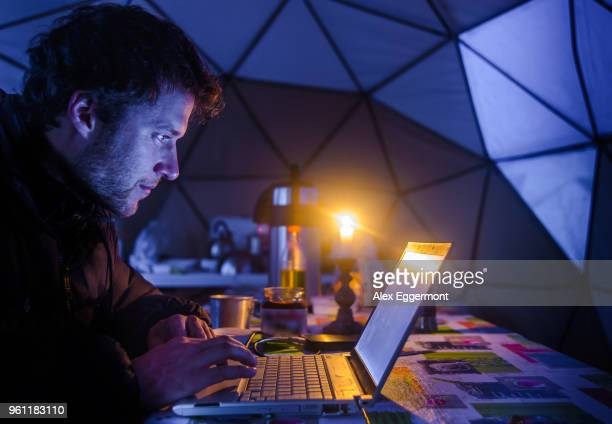 man on expedition, using laptop in camp, fletanes camp, narsaq, kitaa, greenland - remote location stock pictures, royalty-free photos & images