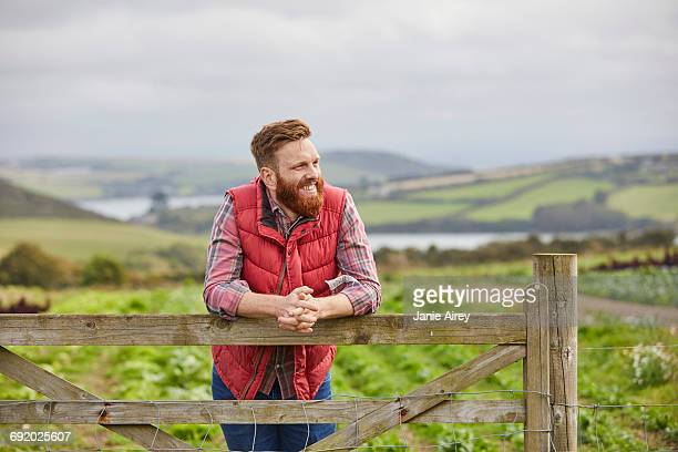 Man on farm leaning against gate looking away