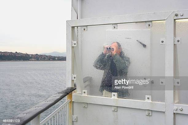 man on ferry looking out to sea through binoculars - binoculars stock pictures, royalty-free photos & images