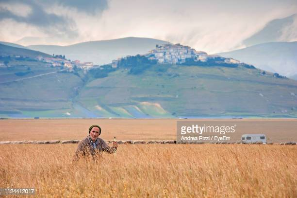 man on field against mountains - andrea rizzi stockfoto's en -beelden