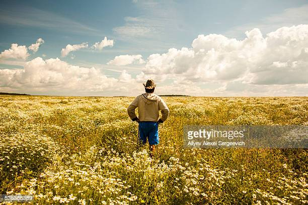 Man on field of wild flowers, Sarsy village, Sverdlovsk region, Russia