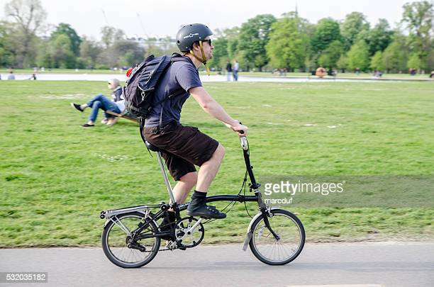 Man on foldable bicycle passing by
