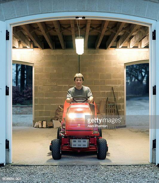 Man on garden tractor sitting in entrance of garage, portrait