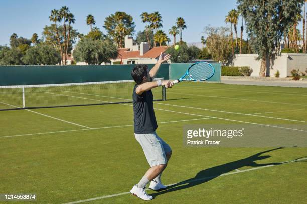 man on grass courts bends knees to make tennis serve - racket sport stock pictures, royalty-free photos & images