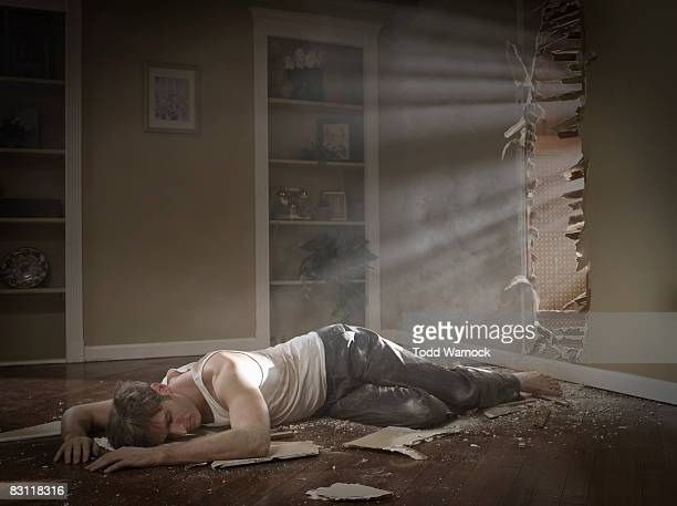 man on ground next to hole in wall