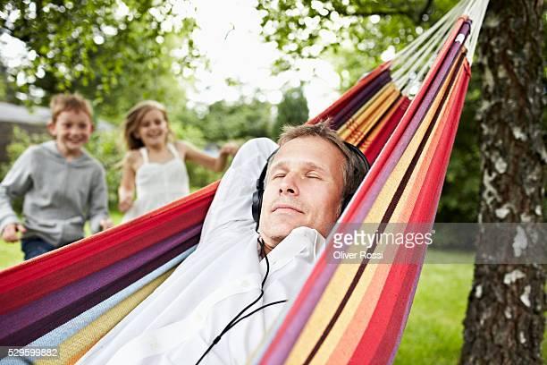 Man on hammock listening music, children (7-9) in background