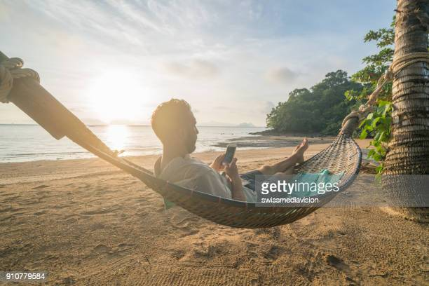 man on hammock using mobile phone, thailand - vacations stock pictures, royalty-free photos & images