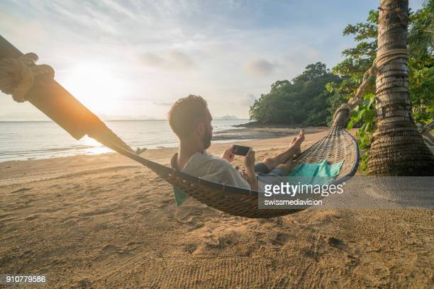 Man on hammock using mobile phone, Thailand
